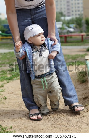 Baby boy takes first steps outdoors in summer