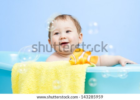 baby boy taking bath in blue tub - stock photo