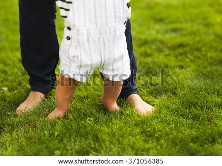 Baby boy taking first steps and mother helping in summer garden