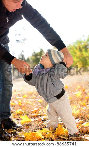 baby boy taking first steps with father help in autumn park - stock photo