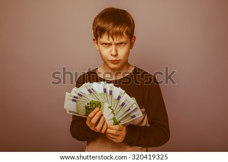 baby boy teenager European appearance brown hair holding bills and wrinkled face on a gray background, greed, anger retro - stock photo