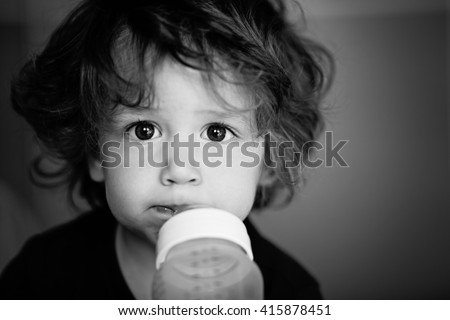 Baby boy/toddler, sucking a bottle of milk. Shallow DOF Black and White - stock photo