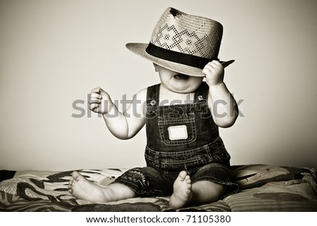 Baby boy under a hat frustrated with the situation. - stock photo