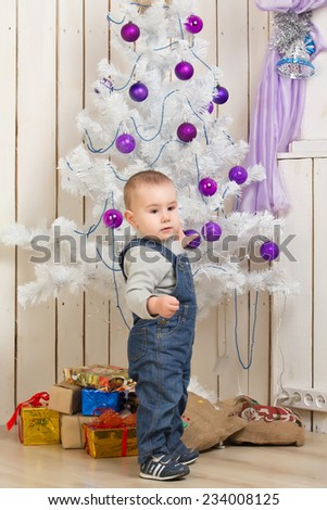 Baby boy under Christmas holiday fir tree with decorations - stock photo