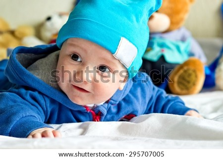 Baby boy weared funny hat with plush teddy bears at blurred background