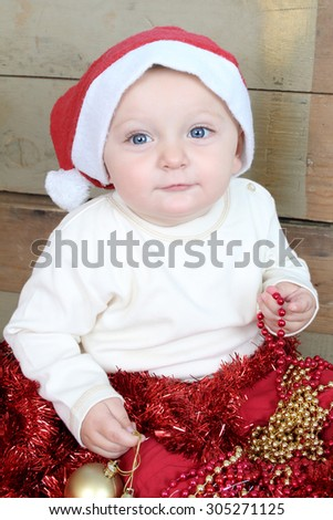 Baby boy wearing a christmas hat playing with decorations - stock photo