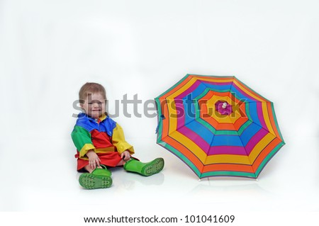 Baby boy, wearing a colorful slicker suit and rubber boots, is sitting besides an open umbrella and crying. - stock photo