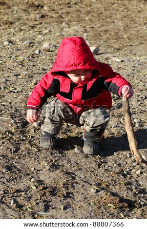 Baby boy wearing a red winter jacket playing outside - stock photo