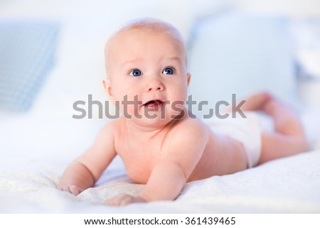 Baby boy wearing diaper in white sunny bedroom. Newborn child relaxing in bed. Nursery for children. Textile and bedding for kids. Family morning at home. New born kid during tummy time with toy bear. - stock photo