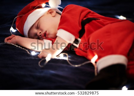 Baby boy wearing Santa outfit sleeping on blue blanket with fairy lights around him.