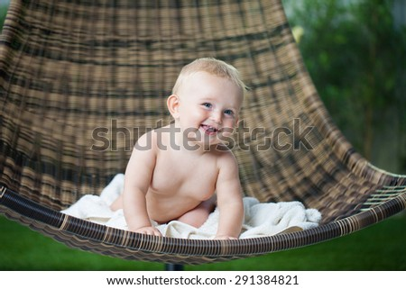 Baby boy with a blanket sitting on the wicker chair - stock photo