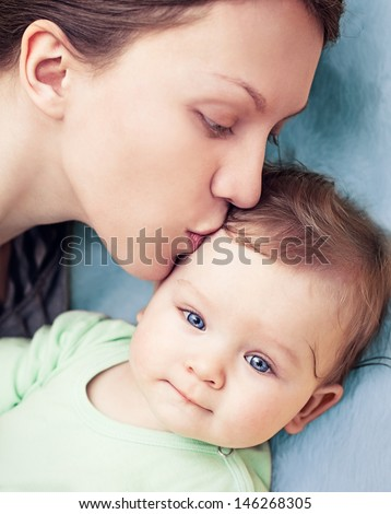 Baby boy with beautiful blue eyes being kissed by his mother. - stock photo
