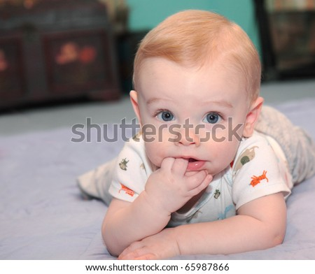 Baby boy with blonde hair and blue eyes learns to crawl,  and plays on floor with fingers in mouth and happy facial expression
