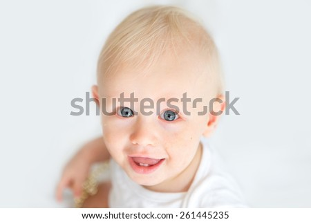 Baby boy with blue eyes looks up at camera against white background - stock photo