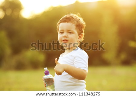 baby boy with brown hair drinking water in the park, holding plastic bottle and showing thumb up. outdoor shot - stock photo
