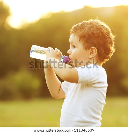 baby boy with brown hair drinking water in the park, holding plastic bottle. outdoor shot - stock photo