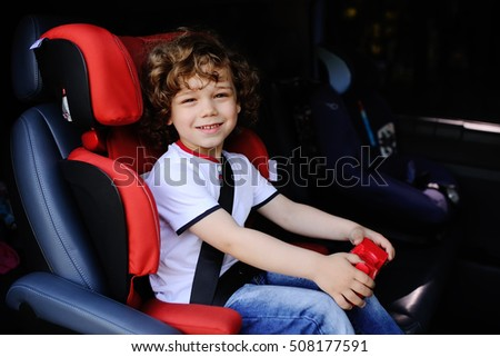 baby boy with curly hair sitting in a child car seat with toy car in the hands of