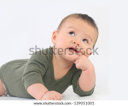 Baby boy with finger in mouth - stock photo