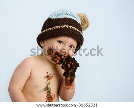 baby boy with hat and cake