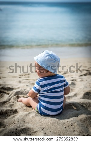 Baby boy with hat sitting on the beach. - stock photo