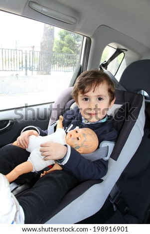 Baby boy with his doll in car seat for safety - stock photo