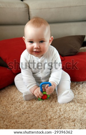 Baby boy with his first toys. Portrait of six months old sweet baby. - stock photo