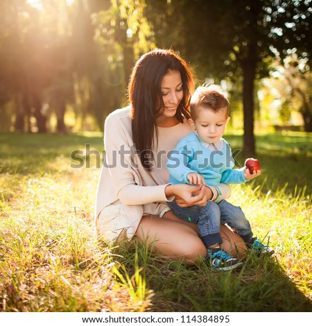 baby boy with his mum in the park - stock photo