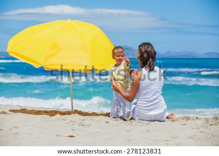 Baby boy with his young mother on tropical beach vacation