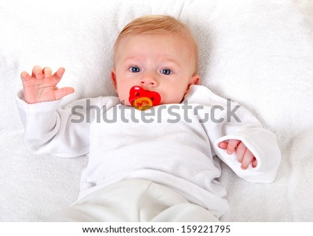 Baby Boy with pacifier lying on the White blanket - stock photo