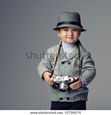 Baby boy with retro camera. - stock photo