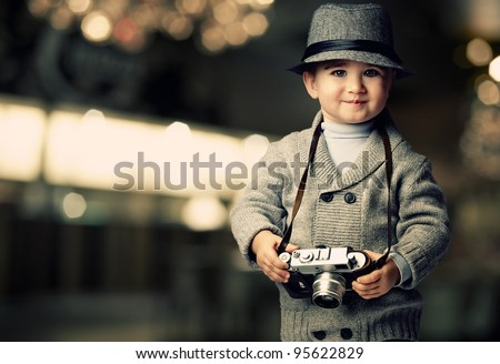 Baby boy with retro camera over blurred background. - stock photo