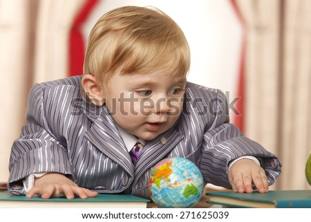 Baby boy with small globe and books - stock photo