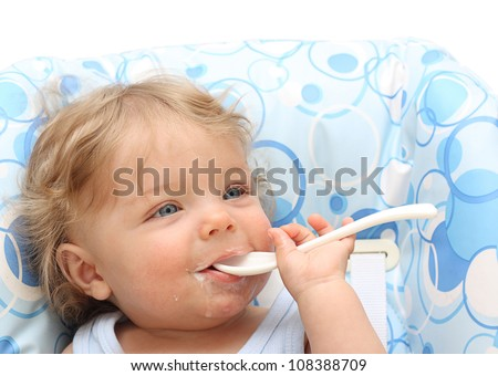 Baby boy with spoon smiling. - stock photo