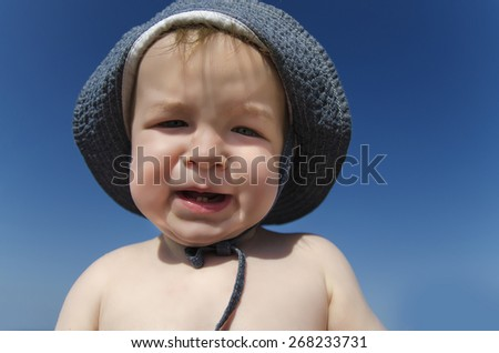 Baby boy with sun hut at the sea beach - stock photo