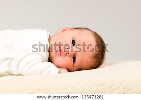Baby boy with white shirts is lying on furry blanket - stock photo