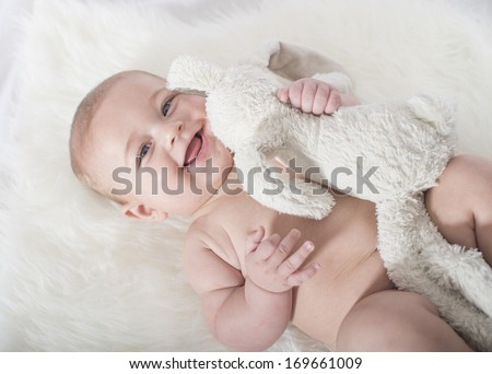 Baby bright photo-shoot on a white blanket and white background - stock photo