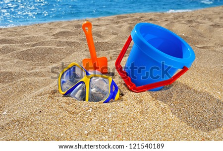 Baby bucket, shovel  and diving mask on the beach against the azure sea - stock photo