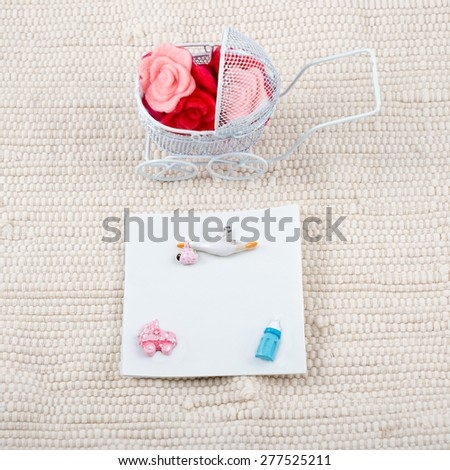 Baby card - baby shower theme. Pram full of flowers on white textile background and a blank signboard with a copy-space for your text. Newborn greeting card. - stock photo