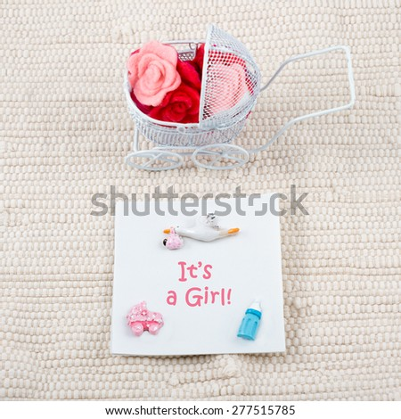 Baby card - Its a girl theme. Pram full of flowers on white textile background. Newborn greeting card. - stock photo