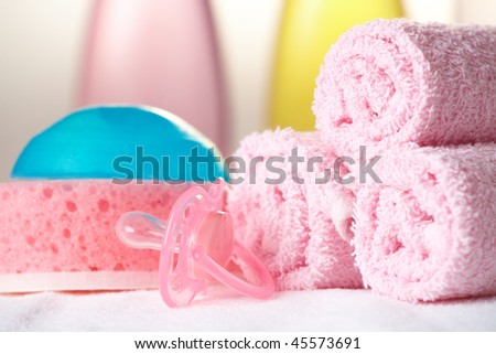 Baby care objects. Olive, shampoo in background towels, sponge, soap and dummy - stock photo