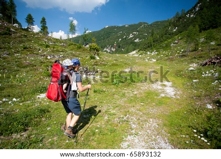 baby carrier in alps, on sunny day, julijan alps, slovenia - stock photo