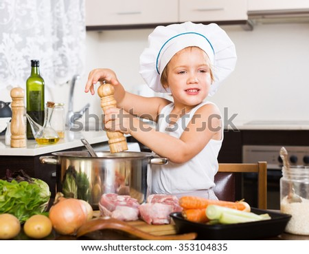 Baby chef prepared soup with vegetables at kitchen