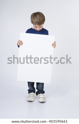 Baby, child boy holding white banner blank, board. Baby boy stands with banner in his hands. Background, branding, mock up - stock photo