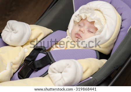 Baby child fastened with security belt in safety car seat. - stock photo