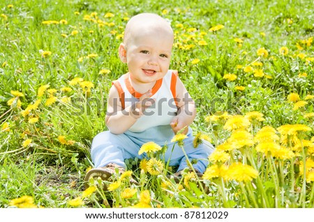 Baby children sitting on the grass in the sun