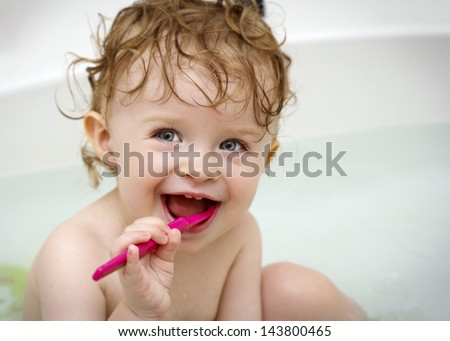 Baby cleaning teeth - stock photo