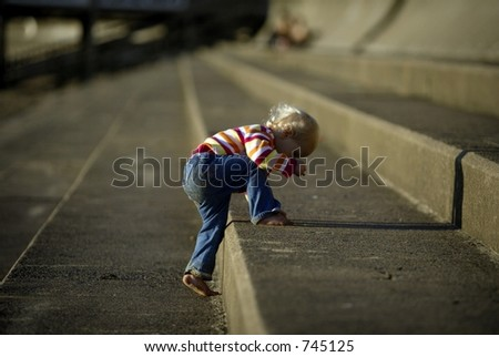 baby climbing up stone steps - stock photo