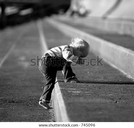 baby climbing up stone steps in black and white - stock photo