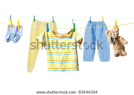 Baby clothes and a tearful teddy bear drying on a rope isolated on white background - stock photo