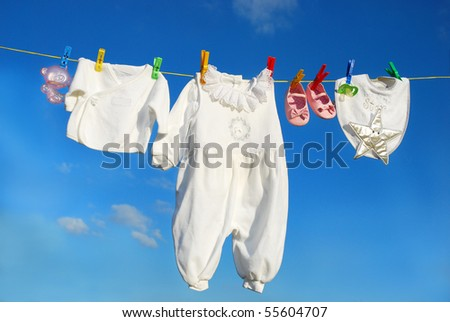 baby clothes and accessories hanging on clothesline against blue sky - stock photo